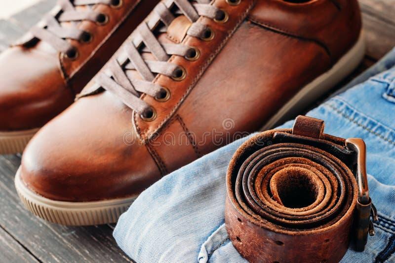 Брайн кроет кожей ботинки ` s людей, пояс и голубые джинсы на темной деревянной предпосылке, конец вверх стоковое фото rf