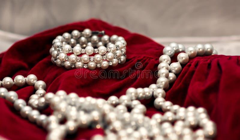Браслет и ожерелье жемчуга на красном бархате, стоковое фото rf