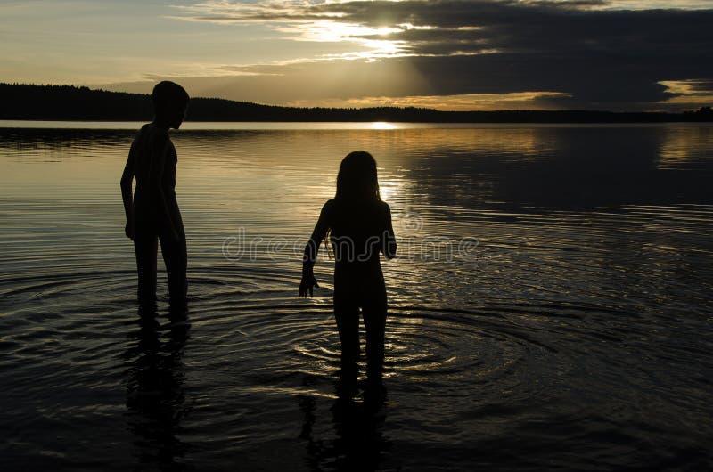 Братья в воде озера на заходе солнца стоковые изображения rf