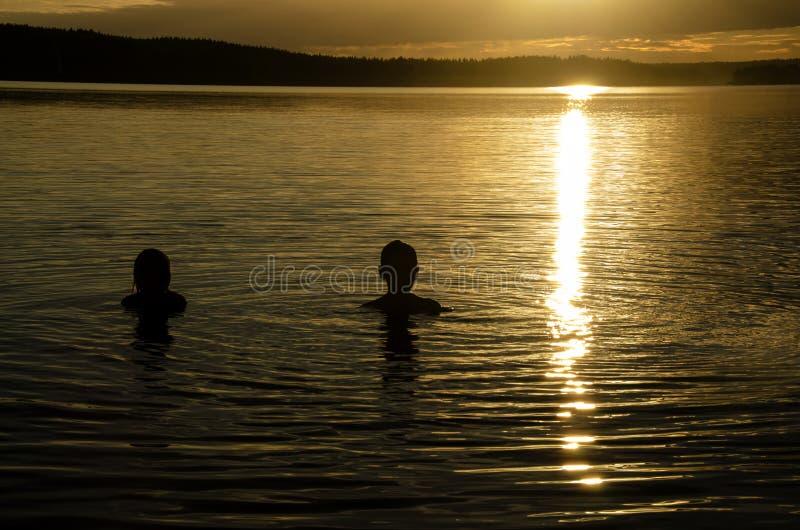 Братья в воде озера на заходе солнца стоковое фото rf