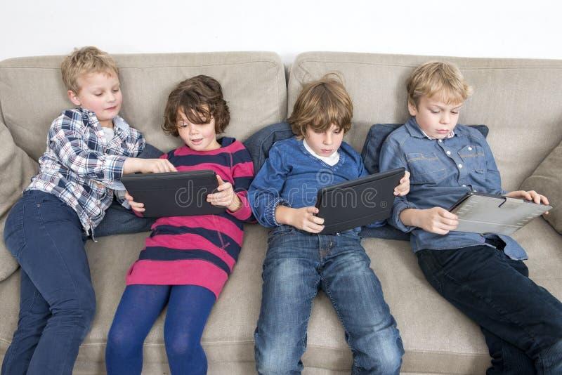 Братья и сестра используя таблетки цифров на софе стоковая фотография rf