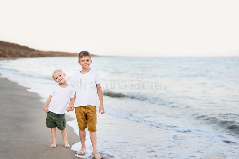 2 брать идут рукой вдоль семейного отдыха морского побережья r стоковые изображения