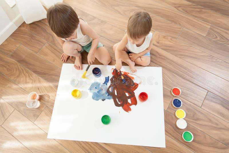 2 брать рисуют краски, сидя на поле стоковое изображение