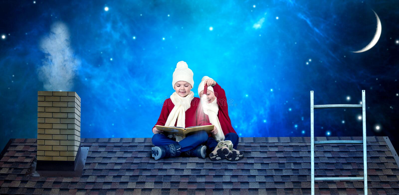 2 брать сидят на ночи рождества на крыше и читают книгу со сказками В ожидании чудеса рождества стоковые изображения rf