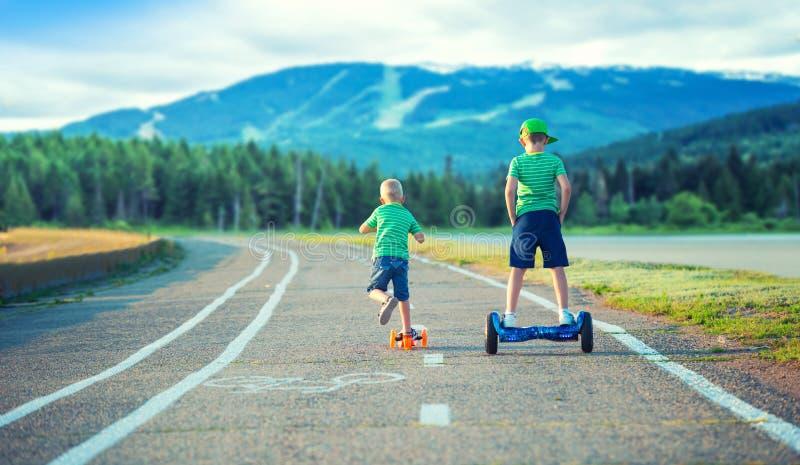 2 брать состязаются кто быстре Одно идет к доске баланса, и второму на самокате стоковая фотография