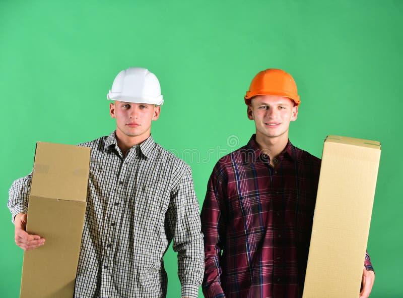 Брат-близнецы в оранжевых и белых шлемах Поставка и склад стоковое фото