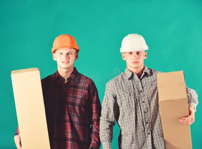 Брат-близнецы в оранжевых и белых шлемах Поставка и склад стоковые фото