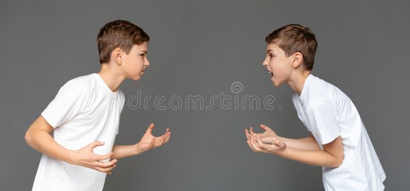 Брат-близнецы имея ссору друг с другом над предпосылкой студии стоковые изображения rf