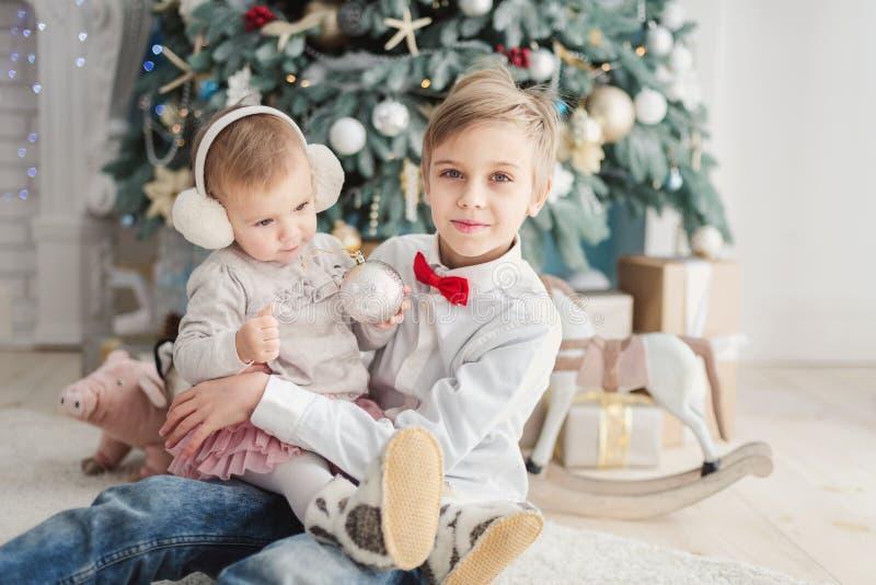 Брат и маленькая сестра под рождественской елкой Усмехаясь мальчик давая подарок рождества девушке Праздник семьи стоковые фото