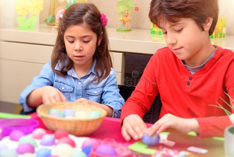 Брат и сестра крася пасхальные яйца стоковые фотографии rf