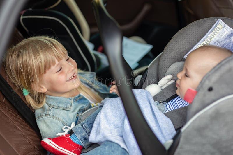 Брат и сестра сидя в автомобиле в месте безопасности Отпрыски на местах пассажира имея потеху совместно во время перемещения мимо стоковое изображение