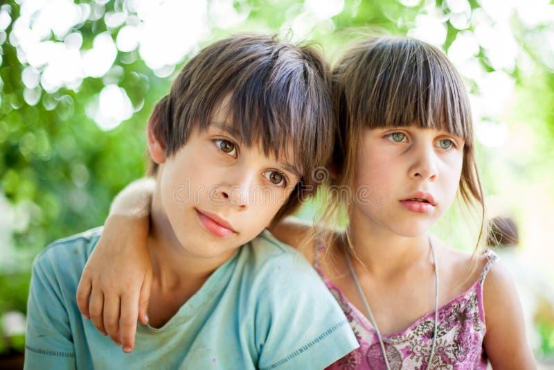 Брат и сестра сидя на стенде в деревне стоковое фото