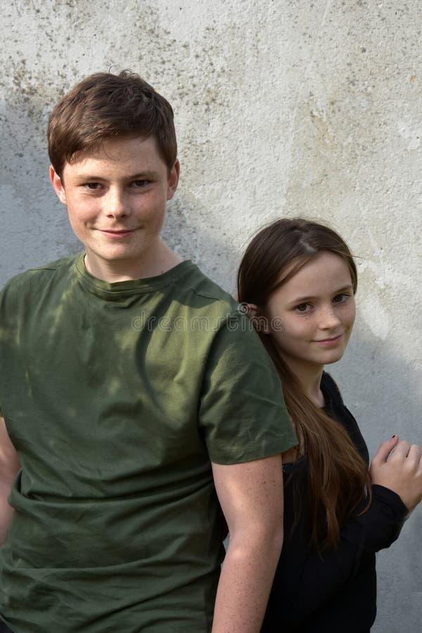Брат и сестра стоят спина к спине стоковая фотография