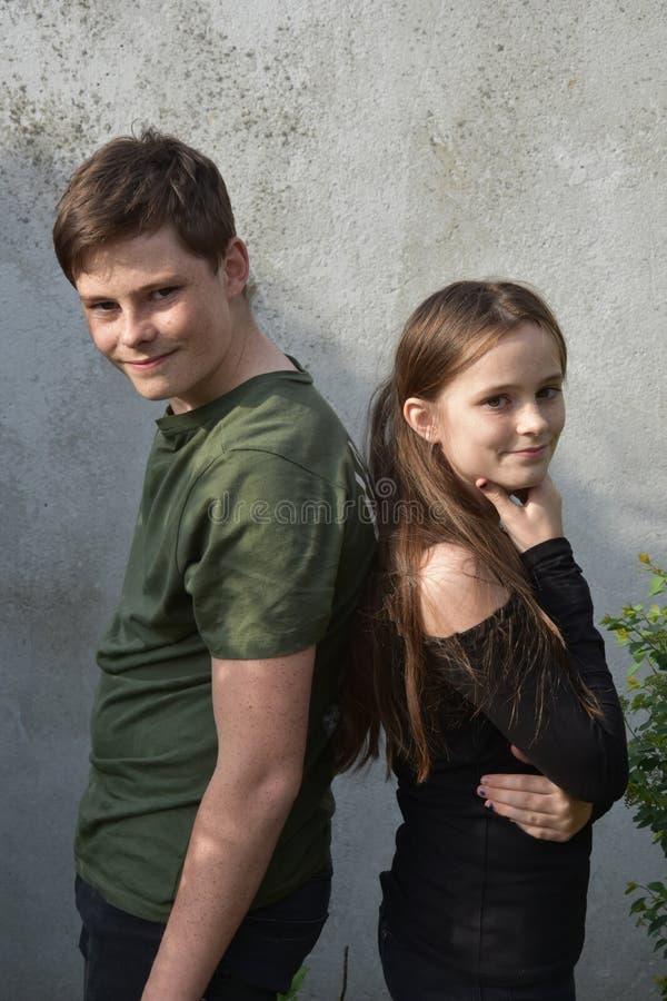Брат и сестра стоят спина к спине стоковое фото rf