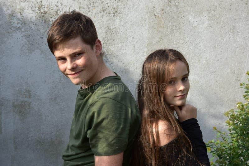 Брат и сестра стоят спина к спине стоковое фото