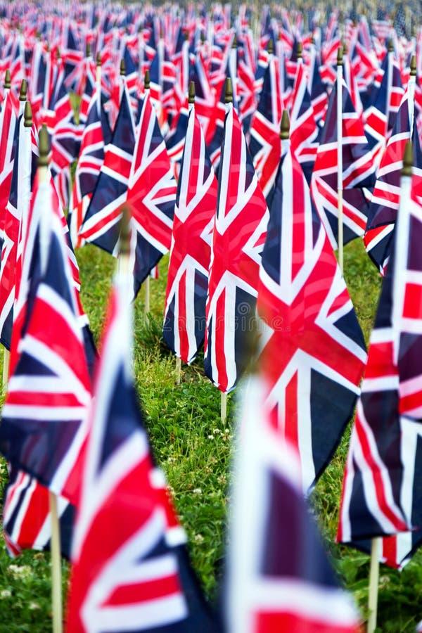 Британцы Великобритания Великобритания сигнализируют в ряд с передним фокусом и дальше символами расплывчатыми с bokeh Флаги были стоковое изображение
