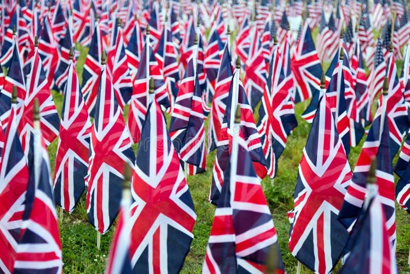 Британцы Великобритания Великобритания сигнализируют в ряд с передним фокусом и дальше символами расплывчатыми с bokeh Флаги были стоковое фото
