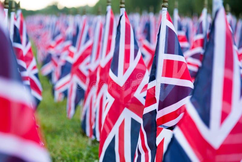 Британцы Великобритания Великобритания сигнализируют в ряд с передним фокусом и дальше символами расплывчатыми с bokeh Флаги были стоковая фотография