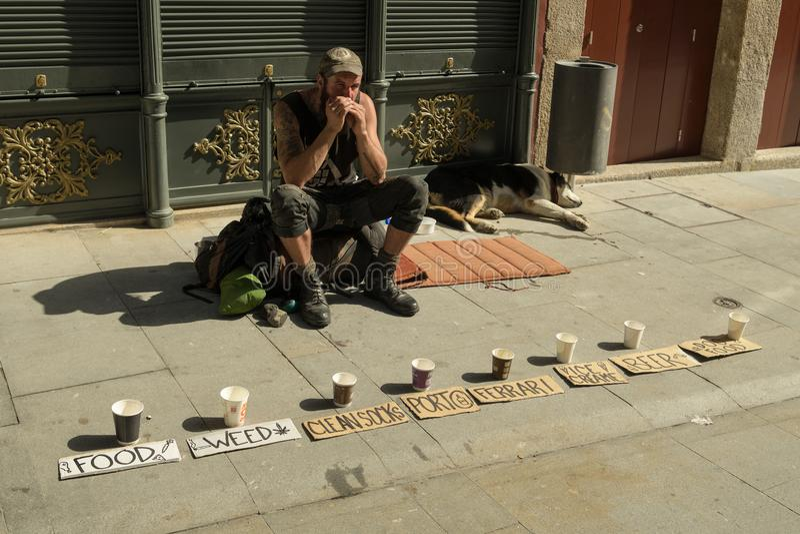 Бродяга детенышей прося деньги в улицах Порту стоковые фото