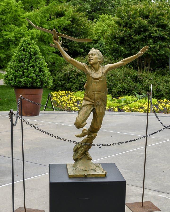 Бронзовая скульптура мальчика с самолетом в его руке ценой Гэри на дендропарке Даллас и ботаническом саде стоковое фото rf