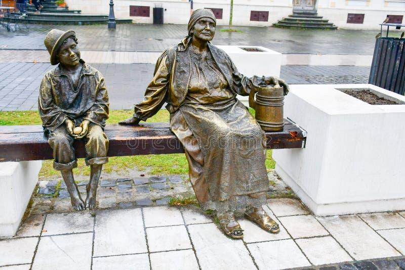 Бронзовая статуя босоногих ребенка и бабушки стоковое фото