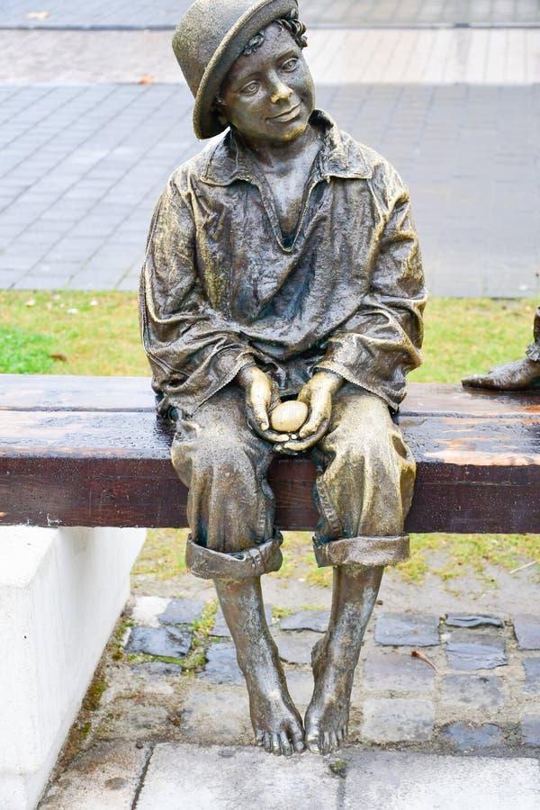 Бронзовая статуя босоногого ребенка держа яичко стоковое фото rf