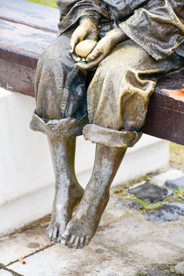 Бронзовая статуя босоногого ребенка держа яичко стоковая фотография rf