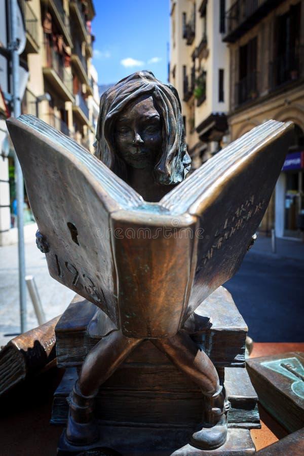 Бронзовая статуя девушки сидя на читать книг стоковое фото
