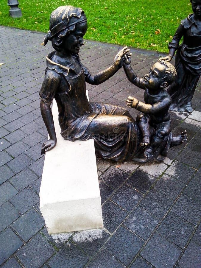 Бронзовая статуя женщины и детей стоковые изображения rf
