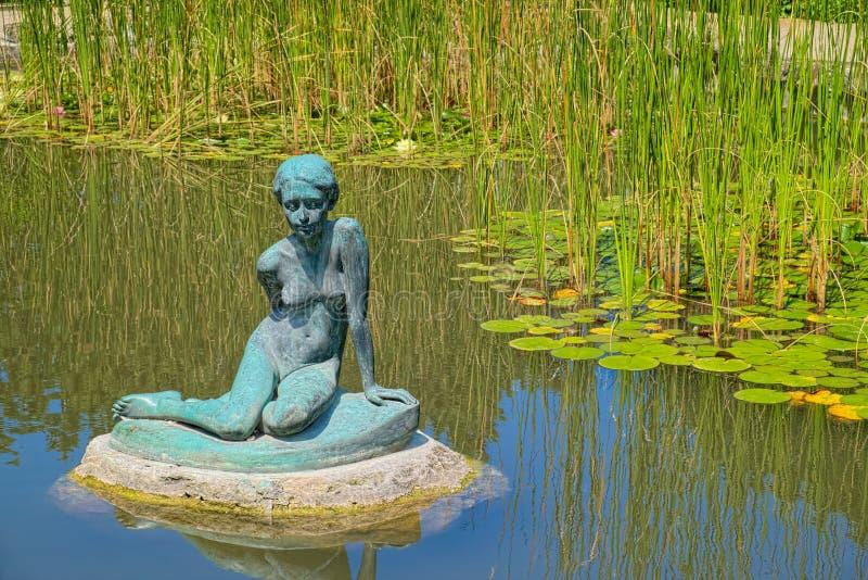 Бронзовая статуя сидя девушки стоковые фото