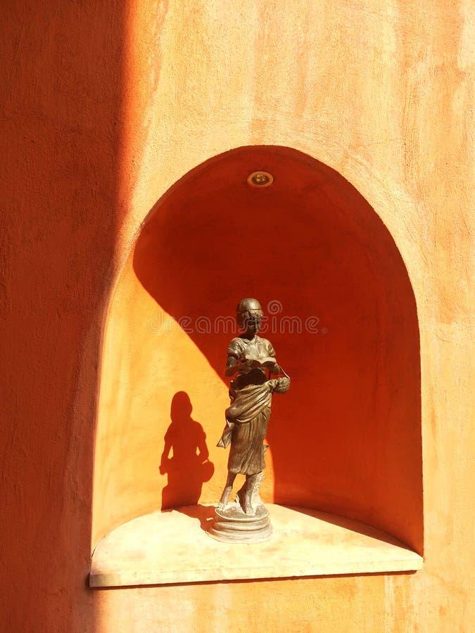 Бронзовая стойка скульптуры женщины читая книгу в изогнутой рамке стоковые фото
