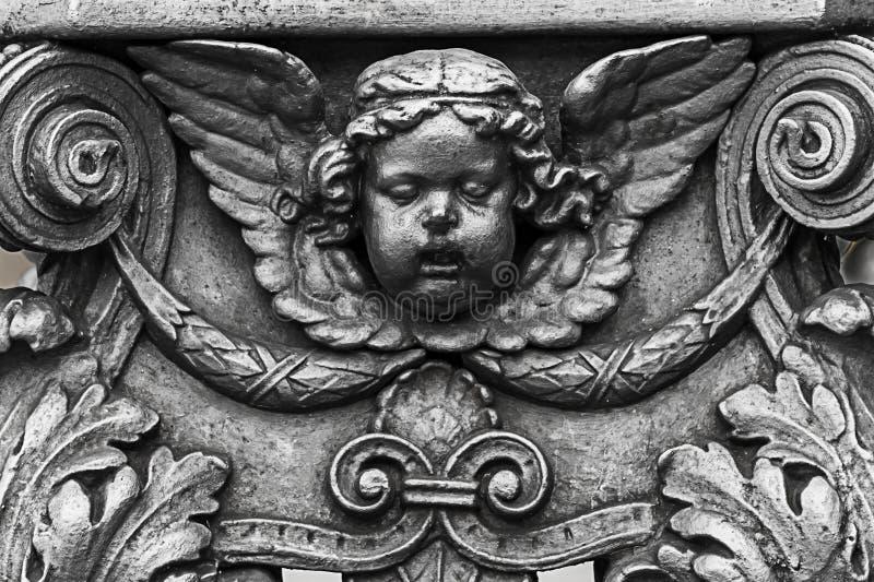 Бронзовые элементы оформления украшая скульптуру головы ангела купидона с вычисляемыми крылами вензелей с vegetable картиной стоковые изображения