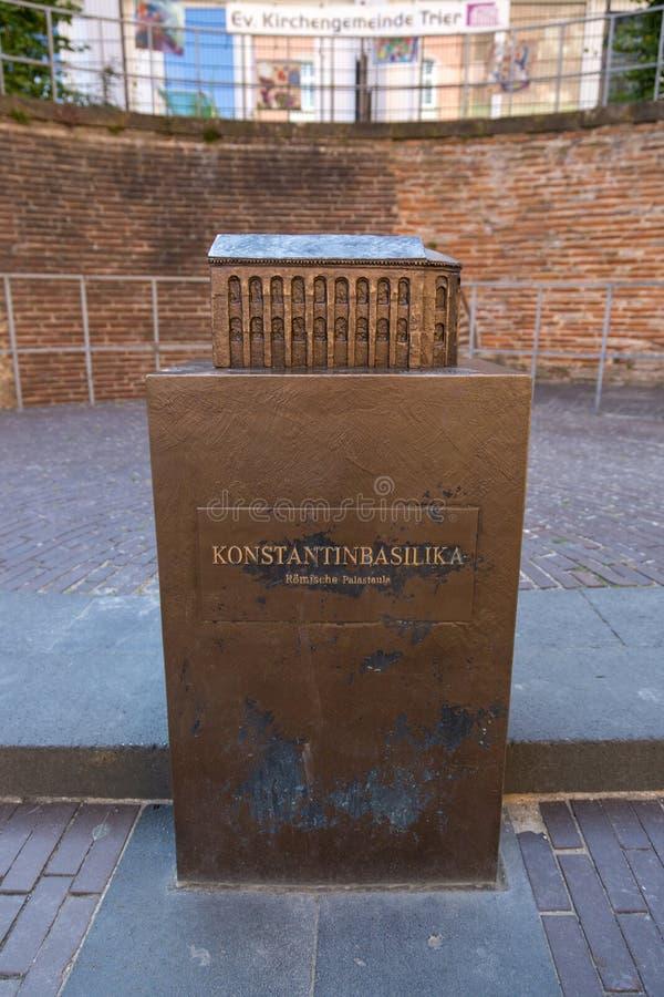 Бронзовый памятник с малым экземпляром здания базилики Константина в центре Трир стоковая фотография