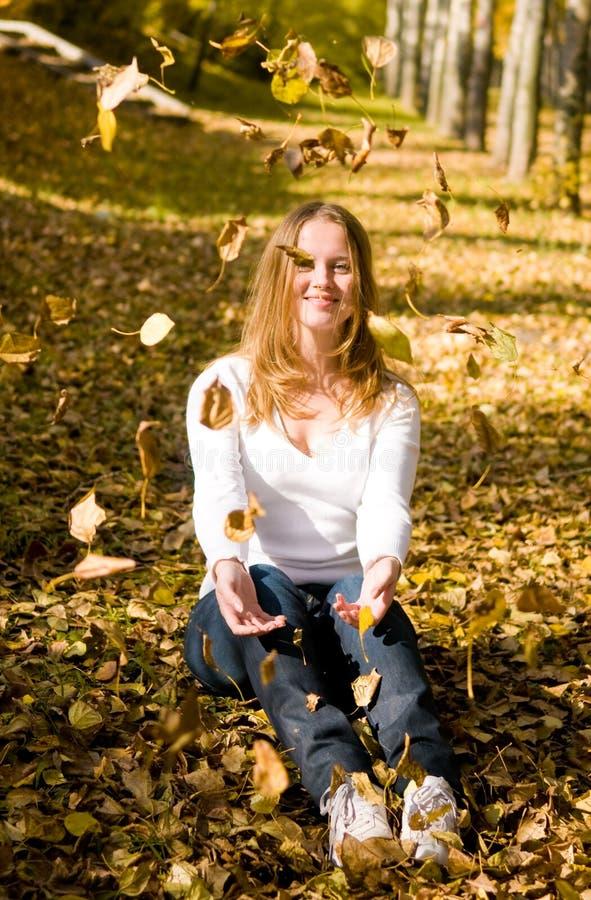 бросать листьев девушки осени счастливый стоковое изображение