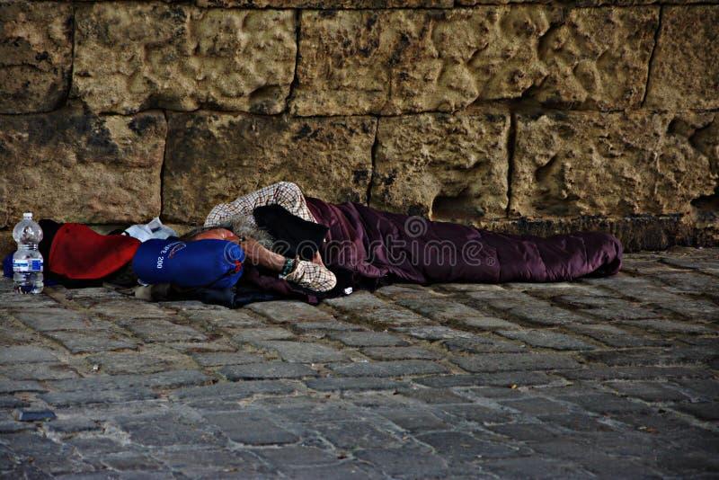 Бродяга спать под мостом Triana в Севилье 1 стоковые изображения