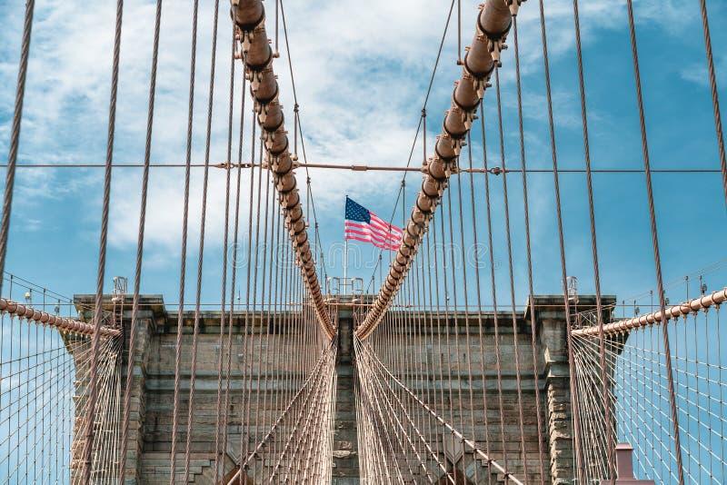 Бруклинский мост и американский флаг против пасмурного голубого неба, Нью-Йорка стоковые изображения