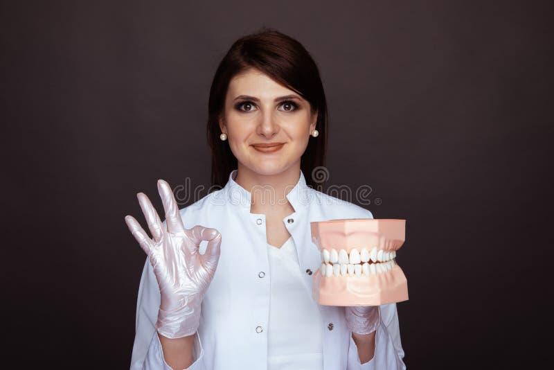 Брунетт: женщина-врач в белых перчатках и униформа, держащая челюсть изолирована стоковые фотографии rf