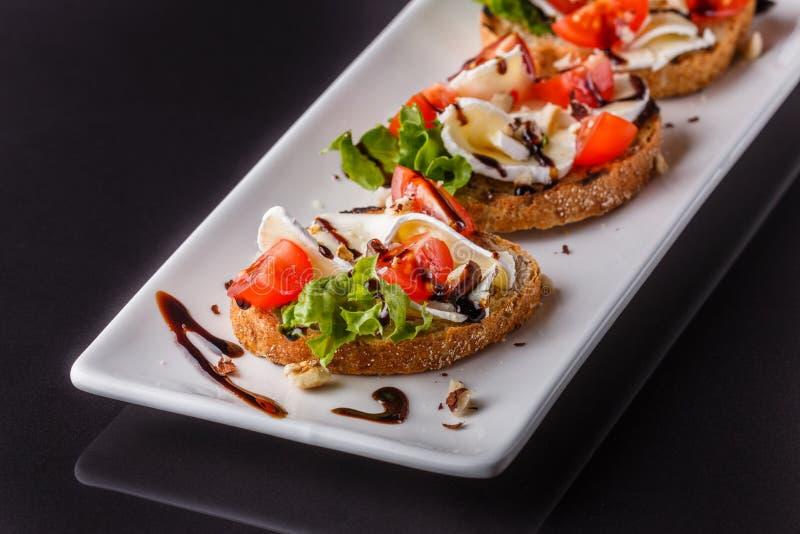 Брушетта с томатами, салатом, камамбертом, бальзамическим уксусом стоковые фото