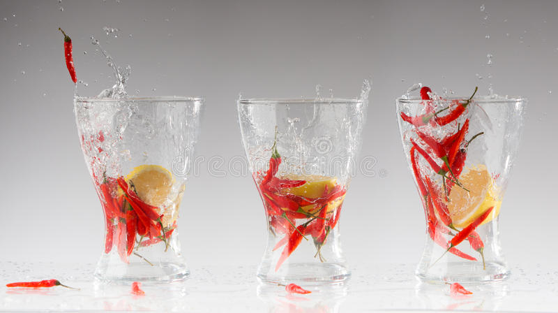 Брызгает воды от накаленных докрасна перца и лимона в стекле стоковые изображения rf