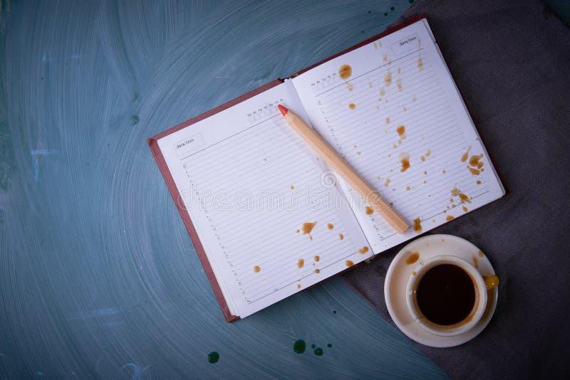 Брызгает кофе на раскрытой тетради Чашка кофе, чашка чая, карандаш На темной предпосылке стоковое изображение