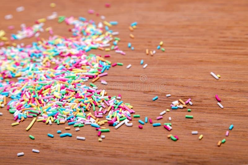 Брызгать цвета Засахарите взбрызните, украшение для торта и пекарня, много брызгает в ведре на деревянной предпосылке стоковое фото rf