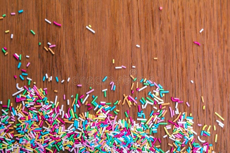 Брызгать цвета Засахарите взбрызните, украшение для торта и пекарня, много брызгает в ведре на деревянной предпосылке стоковое фото