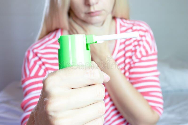 Брызг для боли в горле Фото женщины которая держит брызг в ее руке Концепция здоровья и заболевания стоковое изображение