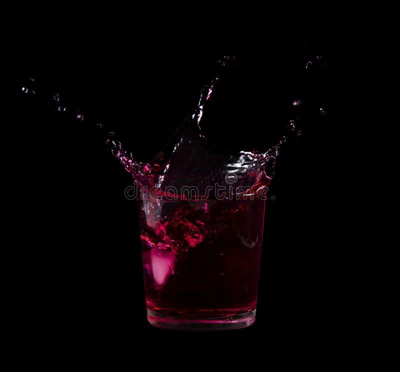 Брызните от куба льда в стекле красной воды или выпейте стоковые изображения rf