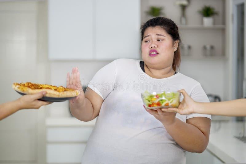 Брюзгливая женщина принимая пиццу салата и выжимк стоковые изображения rf