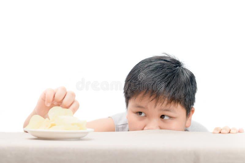 Брюзгливый тучный мальчик достигает хрустящие корочки картошки на таблице стоковая фотография rf