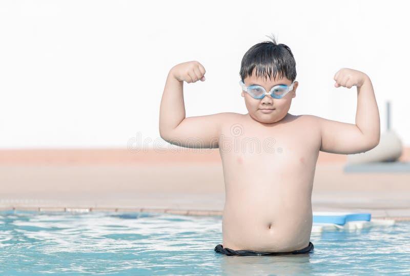 Брюзгливая тучная мышца выставки мальчика в бассейне стоковое фото rf