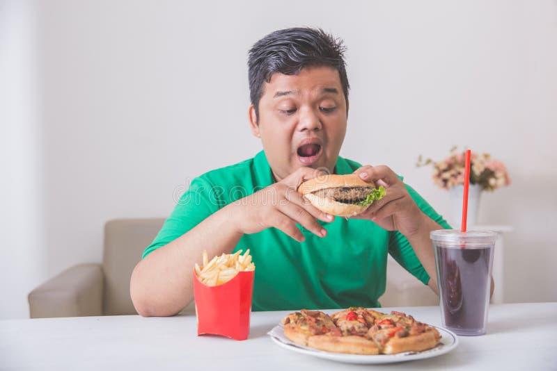 Брюзгливый человек есть высококалорийную вредную пищу стоковые фото