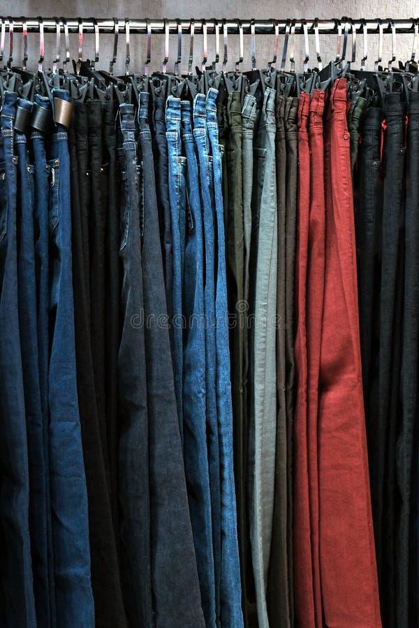 Брюки джинсовой ткани в других цветах на вешалках в магазине одежды Концепция покупок и продаж Предпосылка для дизайна на th стоковые изображения