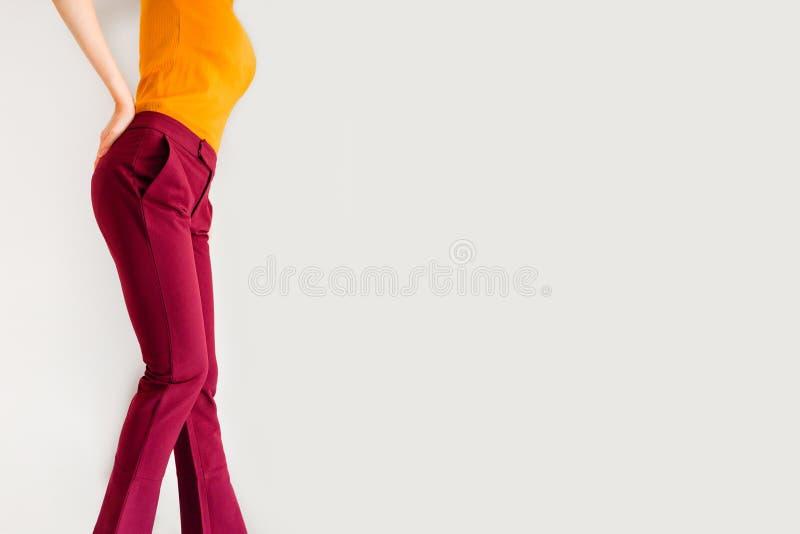 Брюки Красивая молодая женщина в брюках красных или кармина и желтой рубашке представляя на серой предпосылке Взгляд со стороны а стоковые изображения rf